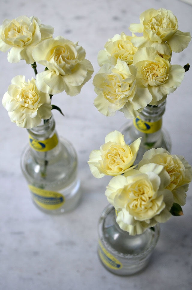 Yellow carnations in lemonade bottles / Totally by Design